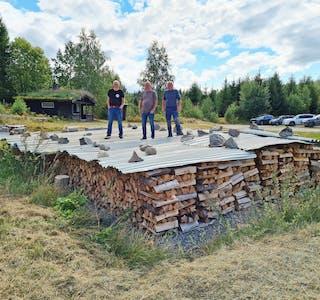 Mesteparten av arbeidet gjenstår: Selv om det allerede er lagt ned en god del arbeid, er det nå den virkelige jobben med å bygge kullmila starter. På toppen av vedkubbene som skal brennes ser vi Gunnar Sanden, Gunleik Aspheim og Erling Susaas.