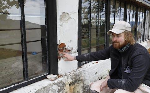 SKADER PÅ BYGNINGEN: Joakim Graneng Pedersen fra Murermester Hansen & Henriksen viser noe av skadene bygningen har fått etter bruk av feil sement noen tiår tilbake.